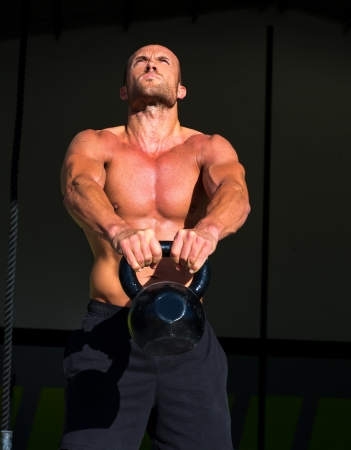 crossfit: Crossfit Kettlebells swing exercise man workout at fitness gym Stock Photo