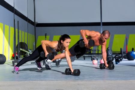 levantamiento de pesas: Gimnasio hombre y la mujer push-up con fuerza pushup mancuerna en un entrenamiento crossfit