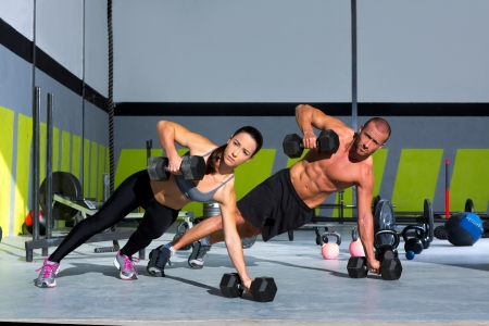 pesas: Gimnasio hombre y la mujer push-up con fuerza pushup mancuerna en un entrenamiento crossfit