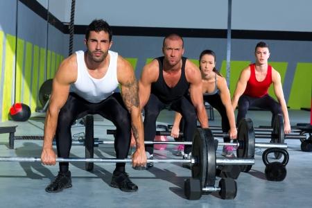 gimnasio grupo con entrenamiento barra de levantamiento de pesas en el ejercicio crossfit