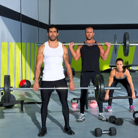 fit: gym group with weight lifting bar workout in crossfit exercise
