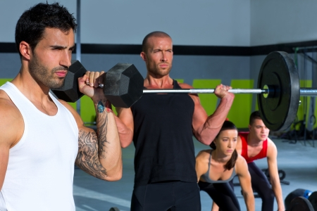 gym group with weight lifting bar and dumbbells workout in crossfit exercise photo