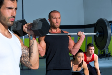 gym group with weight lifting bar and dumbbells workout in crossfit exercise Stock Photo