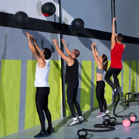 crossfit: Crossfit workout people group with wall balls and rope at fitness gym