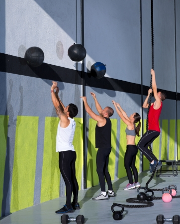 Crossfit workout people group with wall balls and rope at fitness gym photo