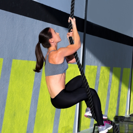 crossfit: Crossfit rope climb exercise in fitness gym workout