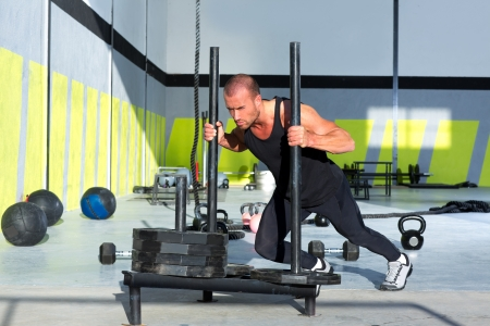 crossfit: Crossfit sled push man pushing weights workout exercise