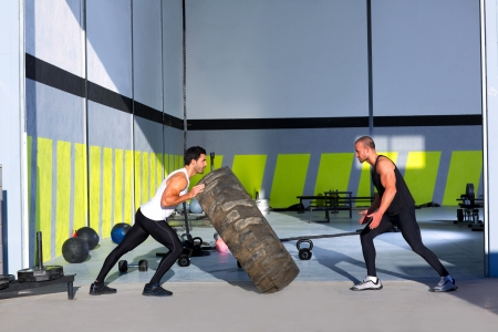flipping: Crossfit flip tires men flipping each other the wheel workout