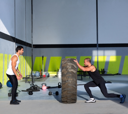 Crossfit flip tires men flipping each other the wheel workout Stock Photo - 17050646