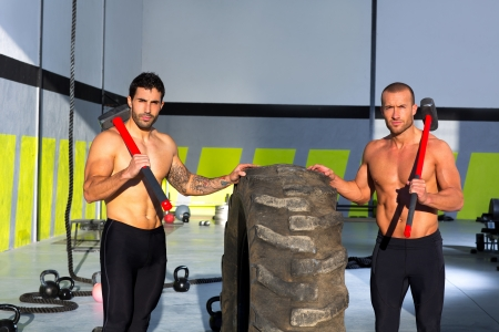 Crossfit sledge hammer men workout at gym posing to camera photo
