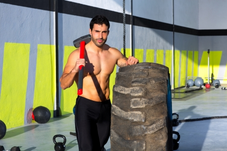 Crossfit sledge hammer man workout at gym relaxed after exercise photo