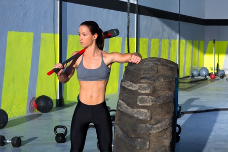 Crossfit sledge hammer woman workout at gym relaxed after exercise photo