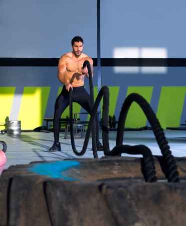 battle cross: Crossfit battling ropes at gym workout from big tires