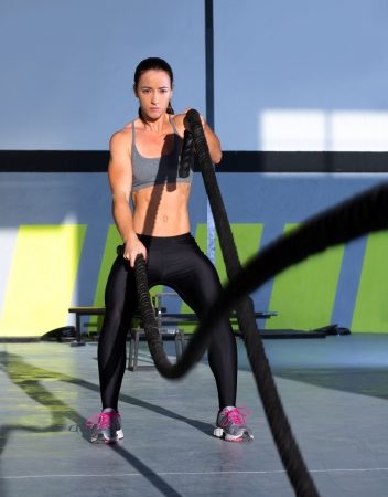 woman rope: Crossfit battling ropes at gym workout fitness exercise