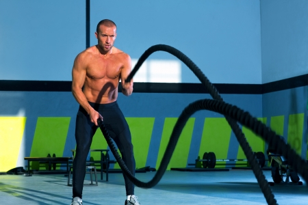 personal trainer: Crossfit battling ropes at gym workout fitness exercise