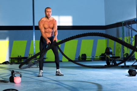 fit man: Crossfit battling ropes at gym workout fitness exercise