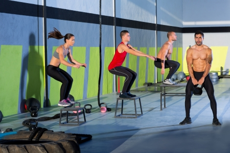 Crossfit box jump people group and kettlebell man at gym