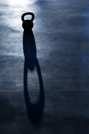 Crossfit Kettlebell weight backlight and shadow on the gym floor Stock Photo - 17058092