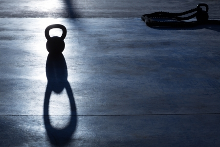 gym floor: Crossfit Kettlebell weight backlight and shadow on the gym floor Stock Photo