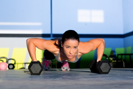 pushup: Gym woman push-up strength pushup exercise with dumbbell in a crossfit workout