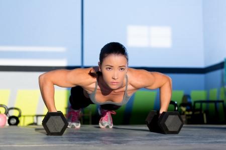 fortaleza: Gym mujer push-up plancha ejercicio de fuerza con pesas en un entrenamiento crossfit Foto de archivo