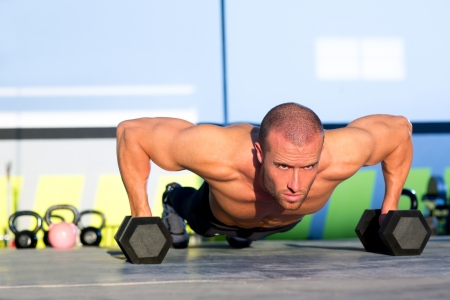 Gym man push-up strength pushup exercise with dumbbell in a crossfit workout Stock Photo - 17050658