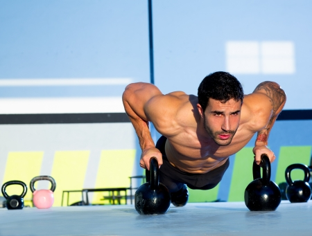 Gym man push-up strength pushup exercise with Kettlebell in a crossfit workout Stock Photo - 17050617