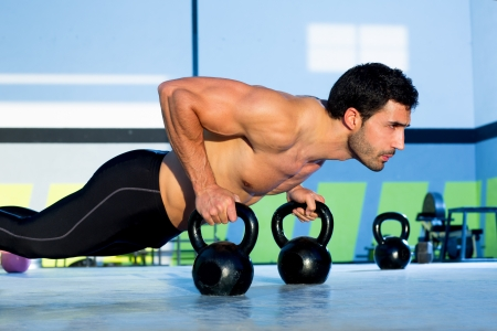 fit man: Gym man push-up strength pushup exercise with Kettlebell in a crossfit workout Stock Photo