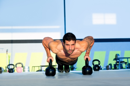 push up: Gym man push-up strength pushup exercise with Kettlebell in a crossfit workout Stock Photo