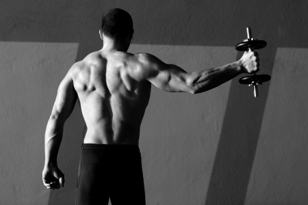 Dumbbell man rear view with back muscles in black and white photo