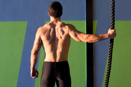 muscular build: Crossfit gym man holding hand a climbing rope rear view