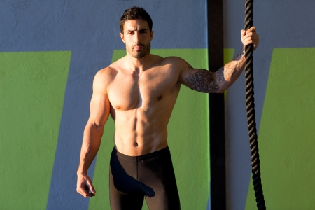 Crossfit gym handsome man holding hand a climbing rope photo