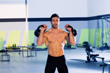 weightlifting equipment: Crossfit man lifting kettlebell workout exercise at gym