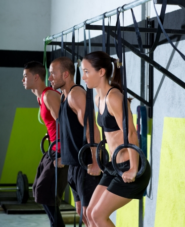 cross bar: Crossfit dip ring group workout at gym dipping in a row exercise