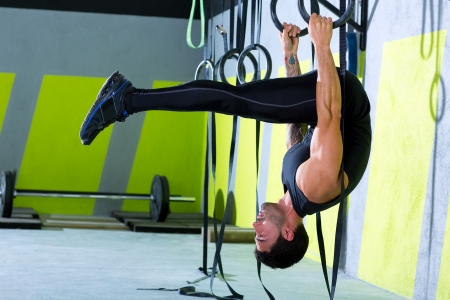 hang body: Crossfit dip ring man workout at gym dipping exercise
