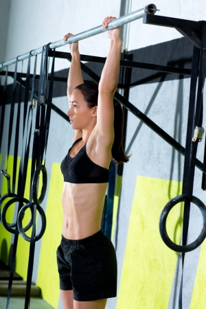 sports bar: Crossfit toes to bar woman pull-ups 2 bars workout exercise at gym Stock Photo