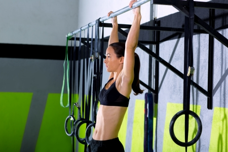 pull up: Crossfit toes to bar woman pull-ups 2 bars workout exercise at gym Stock Photo
