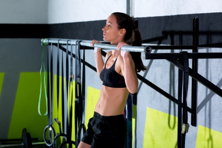 Crossfit toes to bar woman pull-ups 2 bars workout exercise at gym Stock Photo
