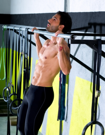 pull: Crossfit toes to bar man pull-ups 2 bars workout exercise at gym Stock Photo