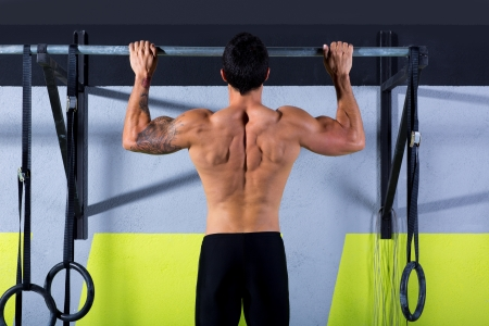 cross bar: Crossfit toes to bar man pull-ups 2 bars workout exercise at gym Stock Photo