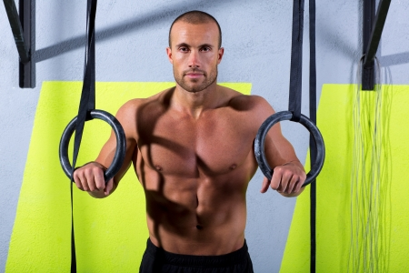 cross bar: Crossfit dip ring man relaxed after workout at gym dipping exercise Stock Photo