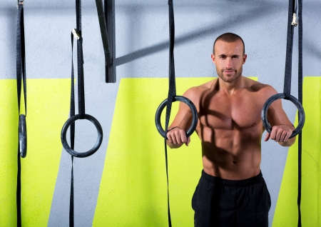 hang body: Crossfit dip ring man relaxed after workout at gym dipping exercise Stock Photo