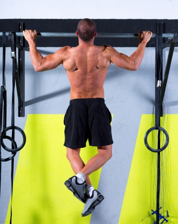 crossfit: Crossfit toes to bar man pull-ups 2 bars workout exercise at gym Stock Photo