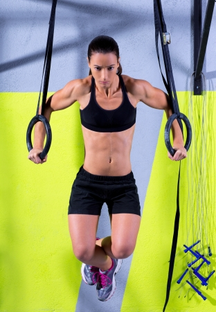 hang body: Crossfit dip ring woman workout at gym dipping exercise