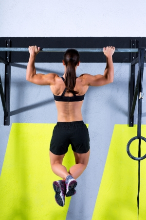 cross bar: Crossfit toes to bar woman pull-ups 2 bars workout exercise at gym Stock Photo