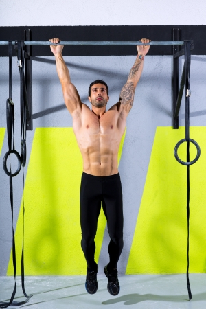 pullups: Crossfit toes to bar man pull-ups 2 bars workout exercise at gym Stock Photo