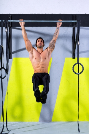 hang body: Crossfit toes to bar man pull-ups 2 bars workout exercise at gym Stock Photo