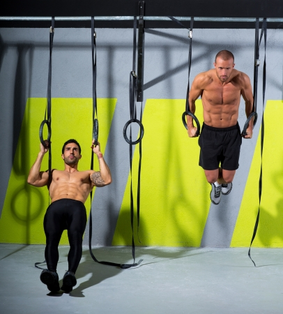 hang body: Crossfit dip ring two men workout at gym dipping exercise