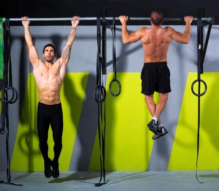 pull up: CrossFit dita di bloccare gli uomini di pull-up allenamento due bar esercizio in palestra Archivio Fotografico