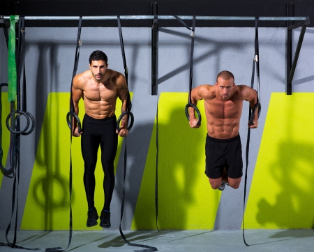 bodybuilder training: Crossfit dip ring two men workout at gym dipping exercise